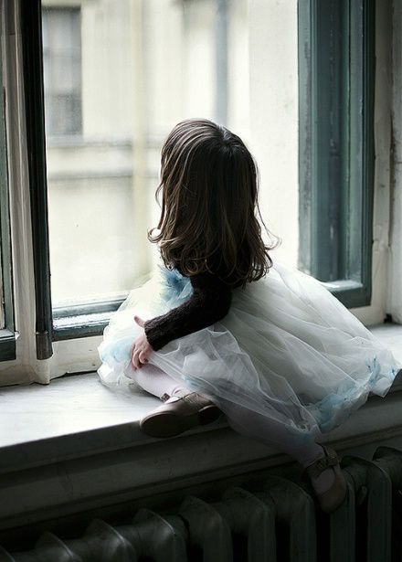 brunette child staring out window